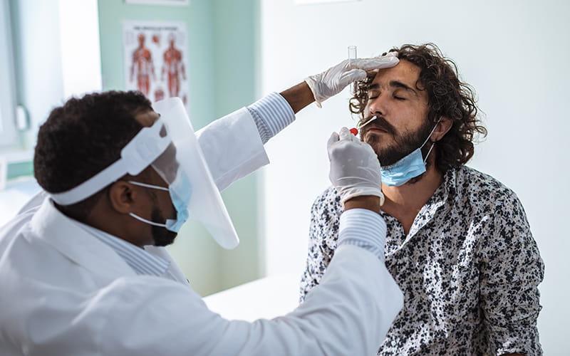 adult man getting COVID-19 test